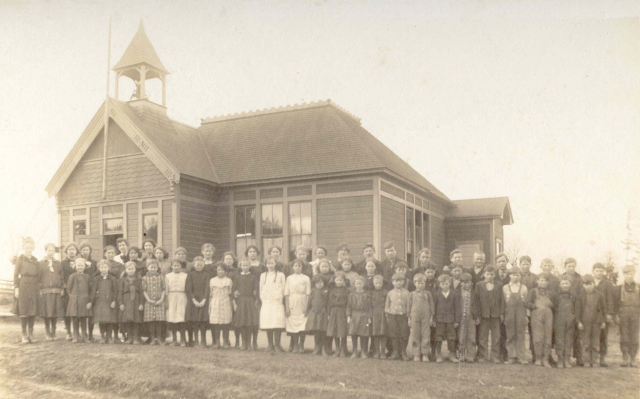 Evergreen Schoolhouse around 1914, give or take a year.  Veneta is the 2nd girl from the left in the front row, Ervin is the 3rd boy from the right in the front row (see below)