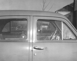 Looking NORTH, Ervin's house is visible over the car's windshield, and the house of his neighbor to the north, E. M. Peer, is visible through the driver's window.